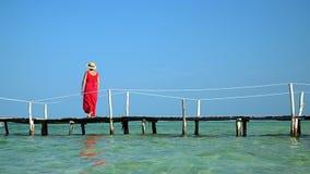 Twee kaders in video Mooie vrouw die onderaan pijler in lange rode kleding lopen Het eiland van Phuquoc De vrouw geniet van menin stock videobeelden