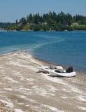 Twee kajaks op zand spugen met huizen op kust Stock Fotografie