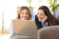 Twee kamergenoten die op online inhoud in laptop thuis letten royalty-vrije stock foto