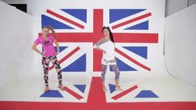 Twee Kaukasische glimlachende meisjes doen het dansen training op achtergrond van Britse vlag stock video