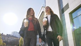 Twee Kaukasische jonge vrouwelijke beste vrienden die vers sap drinken terwijl het lopen in de stad dichtbij een modern gebouw in stock footage