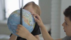 Twee Kaukasische jongens spinnen een bol en een droom over reis stock video