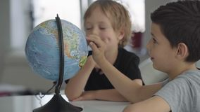 Twee Kaukasische jongens spinnen een bol en een droom over reis stock footage