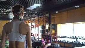 Twee Kaukasische sportvrouw die in de gymnastiek het opheffen gewichten uitwerken stock video