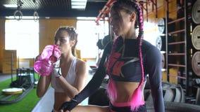 Twee Kaukasische sportvrouw die in de gymnastiek het opheffen gewichten uitwerken stock footage