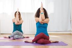 Twee Kaukasische vrouwen die adelaar uitoefenen stellen in yogaklasse Stock Afbeelding