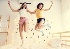 Twee Kaukasische vrouwen die op het bed samen springen stock foto