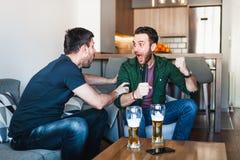 Twee kerels die bier het letten op voetbal drinken royalty-vrije stock afbeelding