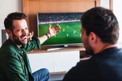 Twee kerels die bier het letten op voetbal drinken stock afbeelding