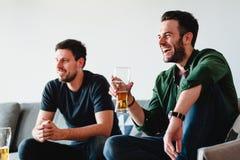 Twee kerels die bier het letten op voetbal drinken royalty-vrije stock foto's