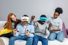 Twee kerels die videospelletjes spelen die de glazen en de meisjes van VR gebruiken steunen hen royalty-vrije stock afbeeldingen