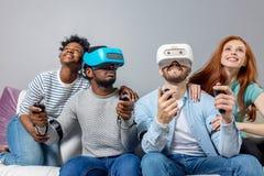 Twee kerels die videospelletjes spelen die de glazen en de meisjes van VR gebruiken steunen hen stock foto