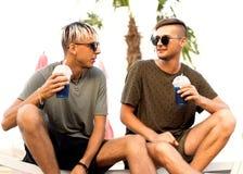 Twee kerels drinken cocktails op een tropisch strand royalty-vrije stock afbeeldingen