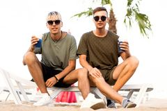Twee kerels drinken cocktails op een tropisch strand royalty-vrije stock afbeelding