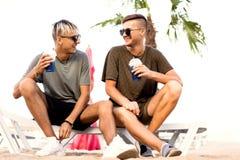Twee kerels drinken cocktails op een tropisch strand stock foto's