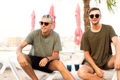 Twee kerels drinken cocktails op een tropisch strand stock afbeelding