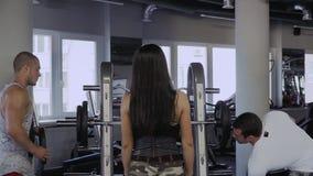 Twee kerels en een meisje in de gymnastiek stock videobeelden