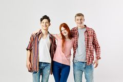 Twee kerels en een meisje in modieuze heldere kleurrijke kleren bevinden zich en glimlach op de witte achtergrond in de studio royalty-vrije stock foto's