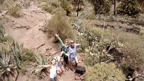 Twee kerels en twee meisjes lanceren een helikopter over het schilderachtige landschap van Spanje De Canarische Eilanden spanje stock footage