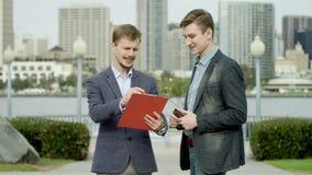 Twee kerels spreken op een straat over één of andere zaken stock footage