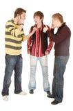 Twee kerels vertellen het derde dat het mobiele gebruik koel is Royalty-vrije Stock Foto's