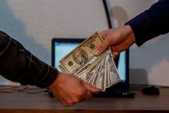 Twee kerels of zakenlieden die dollars geven aan elkaar Laptop binnen stock afbeeldingen