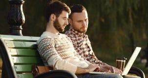Twee kerels zitten op een bank en open laptop die en schrijven 4k spreken stock videobeelden