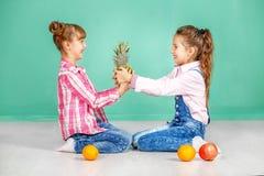 Twee kinderen bepleiten ananas Zusters in jeans Het concept Royalty-vrije Stock Foto's