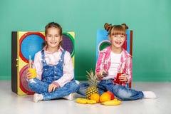 Twee kinderen bepleiten ananas Zusters in jeans Het concept Royalty-vrije Stock Afbeelding