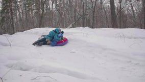 Twee kinderen berijden op een sneeuwheuvel op een slee De kinderen vallen met een slee Sporten en openluchtactiviteiten stock video