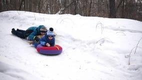 Twee kinderen berijden op een sneeuwheuvel op een slee De kinderen vallen met een slee Sporten en openluchtactiviteiten stock videobeelden