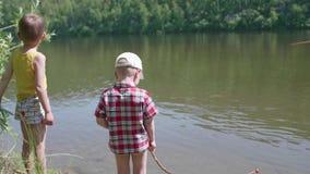 Twee kinderen bevinden zich op de rivierbank In de handen van kinderenstaven De hete Dag van de Zomer stock footage