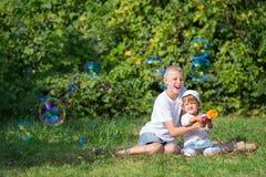 Twee kinderen blazen bellen Stock Foto's