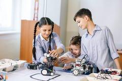 Twee kinderen, broer met zuster het enaging in hun hobby-construerende robotspeelgoed stock foto's