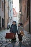 Twee kinderen, de jongensbroers, de dragende koffer en het hondstuk speelgoed, reizen in de alleen stad royalty-vrije stock foto