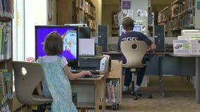 Twee kinderen die de computers met behulp van bij de bibliotheek stock video