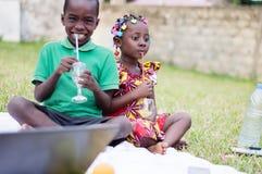 Twee kinderen die en sap zitten drinken stock afbeelding