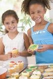 Twee kinderen die in keuken koekjes verfraaien Stock Foto