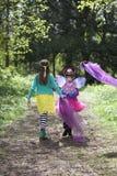 Twee kinderen die langs een bosweg lopen Stock Foto