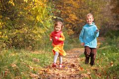 Twee kinderen die op houten de herfstvoetpad in werking worden gesteld royalty-vrije stock foto's