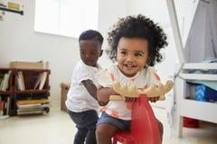Twee Kinderen die op Rit op Toy In Playroom zitten stock fotografie