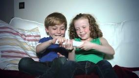 Twee Kinderen die op Sofa Arguing Over-Verre TV zitten stock footage