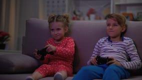 Twee kinderen die spel met bedieningshendels gevangen ouders spelen bij nacht, vermaak stock video