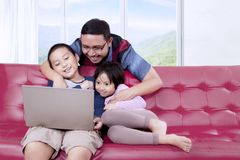Twee kinderen die van een film met hun vader genieten stock afbeeldingen