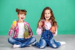 Twee kinderen drinken sap en verheugen zich Meisjes met ananas en p Stock Afbeeldingen