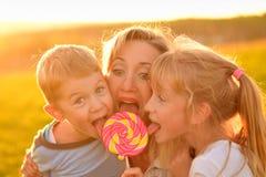 Twee kinderen eten lolly met moeder Stock Foto's