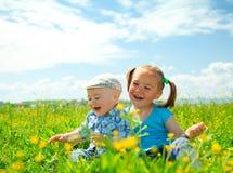 Twee kinderen hebben pret op groene weide Royalty-vrije Stock Afbeeldingen