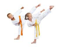 Twee kinderen in karategi slaat Yoko-geri Royalty-vrije Stock Fotografie