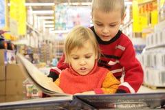 Twee kinderen kijken boek in opslag Royalty-vrije Stock Foto's