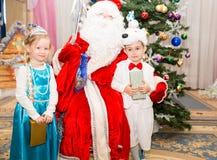 Twee kinderen kleedden zich in Carnaval-kostuums met Santa Claus dichtbij Kerstmisspar Royalty-vrije Stock Afbeeldingen